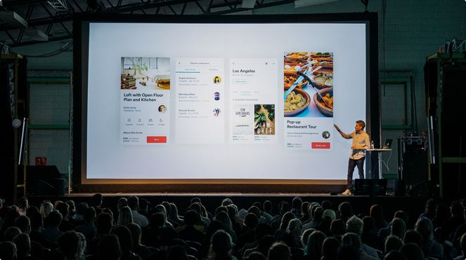 Man presenting slide on stage in front of a big audience