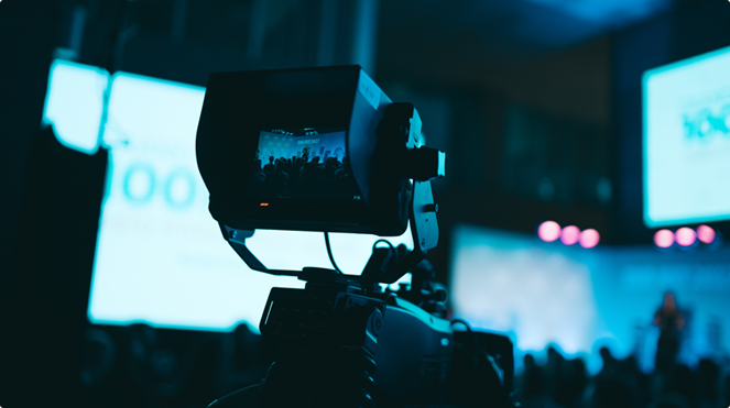 Close-up of a camera filming a stage at event